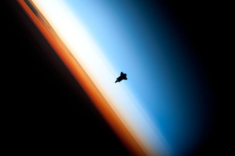 Снимка на силуета на совалката Индевър, която в момента на заснемането се намера над южния Пасифик. Оранжевия слой е тропосферата, в която се генерират всички известни ни климатични феномени. Тя преминава към по-светлата стратосфера, която пък се прелива в мезосферата (кликни за по-голяма версия). Снимка: НАСА