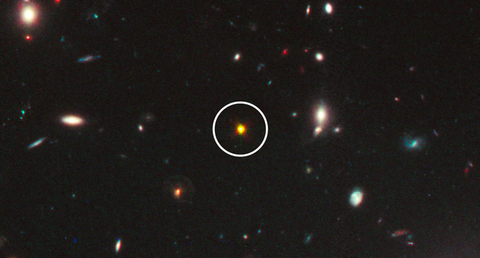 Снимка в инфрачервения диапазон на един от най-далечните и мощни квазари (в бялото кръгче) откривани до сега. Поради дистанцията го виждаме така както е изглеждал по-малко от милиард години след Големия взрив. Снимка: NASA/ESA/M. Mechtley, R. Windhorst, Arizona State University