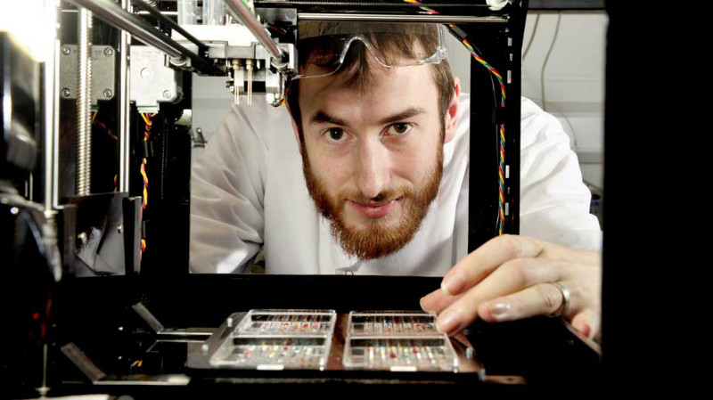 Докторантът по биоинженерство Алън Фолкнър-Джоунс позира с 3D принтера, който учените използват за да принтират човешки ембрионални стволови клетки. Снимка: Humans Invent