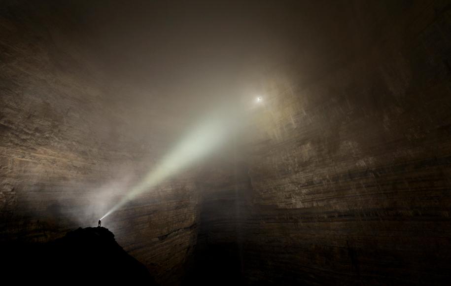 Човекът, осветяващ огромна зала от пещерния комплекс Ър Ван Дун, изглежда като миниатюрна играчка. Снимка: Robbie Shone
