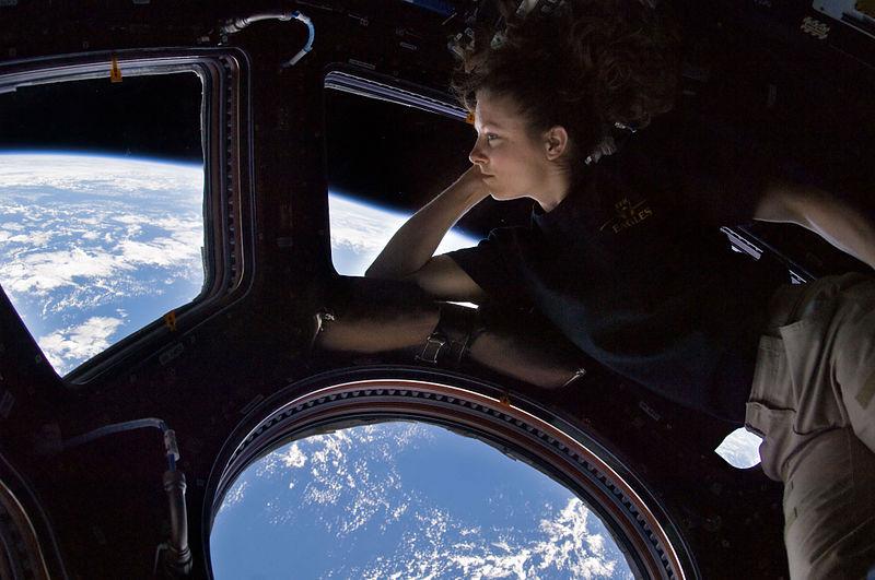 """Астронавтката Трейси Дайсън от Експедиция 24 до Международната космическа станция гледа през прозорците на модула """"Купола"""". Снимка: NASA"""