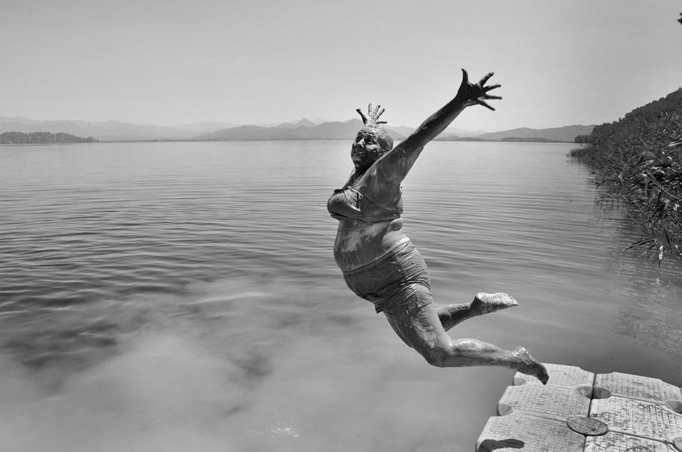 Тази широко усмихната жена пожелала да я снимат докато скача в езерото, малко след като приключила с калната си баня. Фотографията е направена във Фетие, Турция. Снимка: © Alpay Erdem, Turkey, Winner, Smile, Open Competition, 2014 Sony World Photography Awards