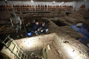Археолозите Робин Кънингам (вляво) и Кош Прасад Ачария ръководят разкопките в Лумбини. На заден план се виждат медитиращи монаси. Снимка: Ira Block/National Geographic