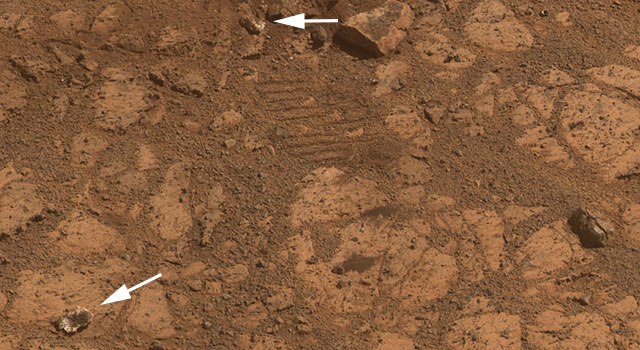 """Тази нова снимка показва, че мистериозно появилият се камък (стрелката долу) е фрагмент от друг камък (стрелката горе). Следите от веригите показват, че камъкът се е разчупил на две при преминаването на """"Опортюнити"""" през него. Снимка: NASA/JPL-Caltech/Cornell Univ./Arizona State Univ."""